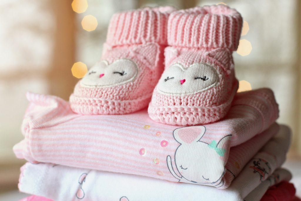 Chaussons de couleur rose avec un motif de chouettes empilés sur des vêtement pour fille