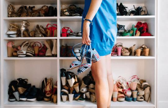femme devant placard plein de chausures avec une paire de sandales à talons à la main
