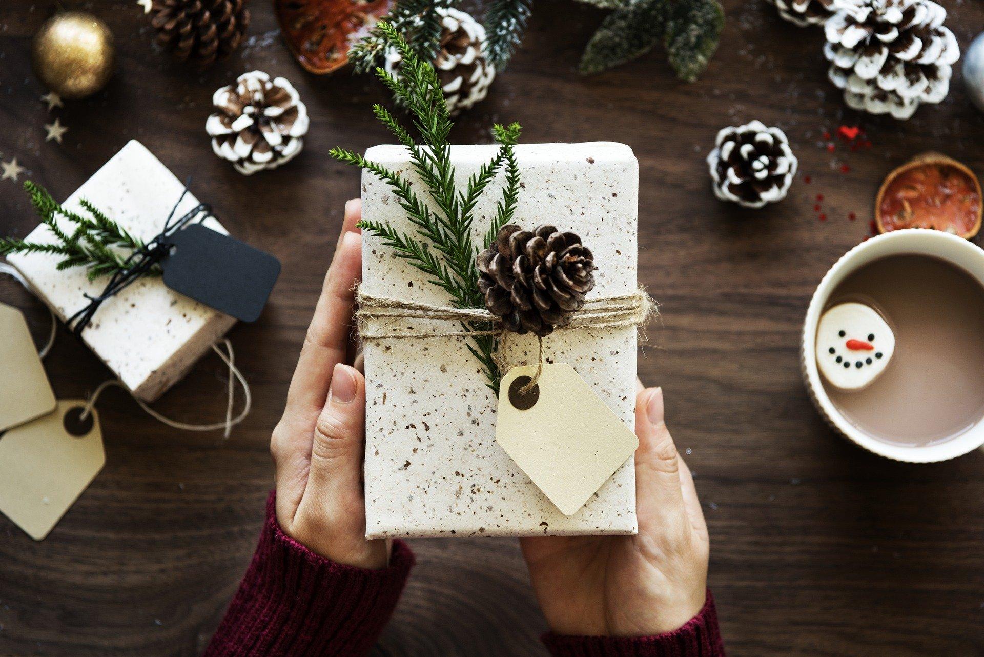 Femme qui tient un paquet cadeau de Noël au-dessus d'une table en bois décorée avec des pommes de pin