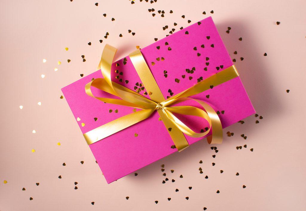 cadeau avec papier rose et ruban doré et paillettes parsemées