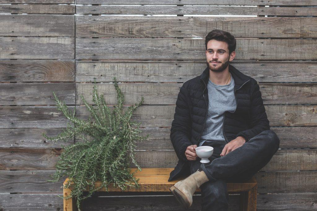 homme brun portant un t shirt gris sous une doudoune foncée un jean et des boots claires avec une tasse à la main