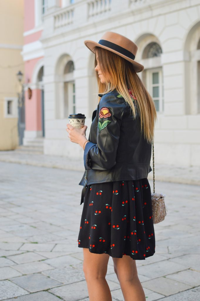 femme blonde portant une veste en cuir avec une fleur sur le bras sur une robe noir imprimé et un chapeau