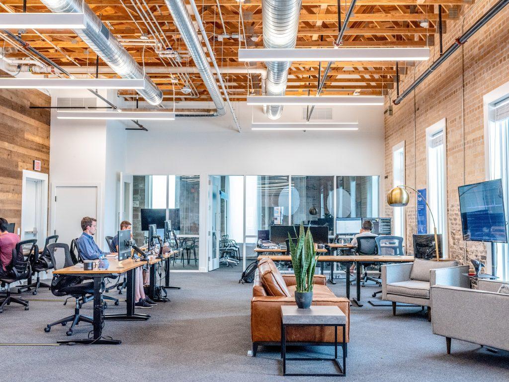 entreprise décorés façon industrielle avec bureaux canapé et plante