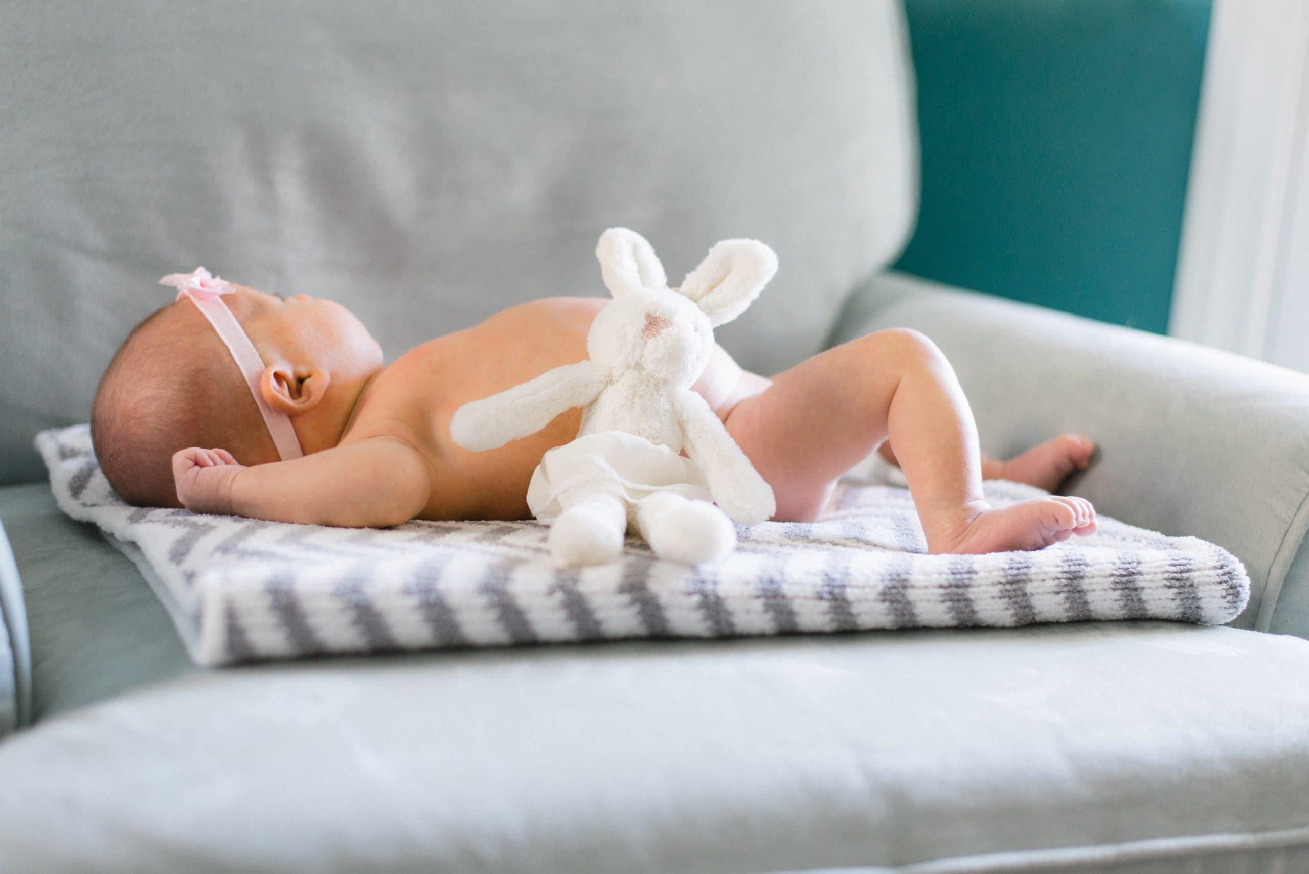 Bébé avec un doudou offert en cadeau de naissance