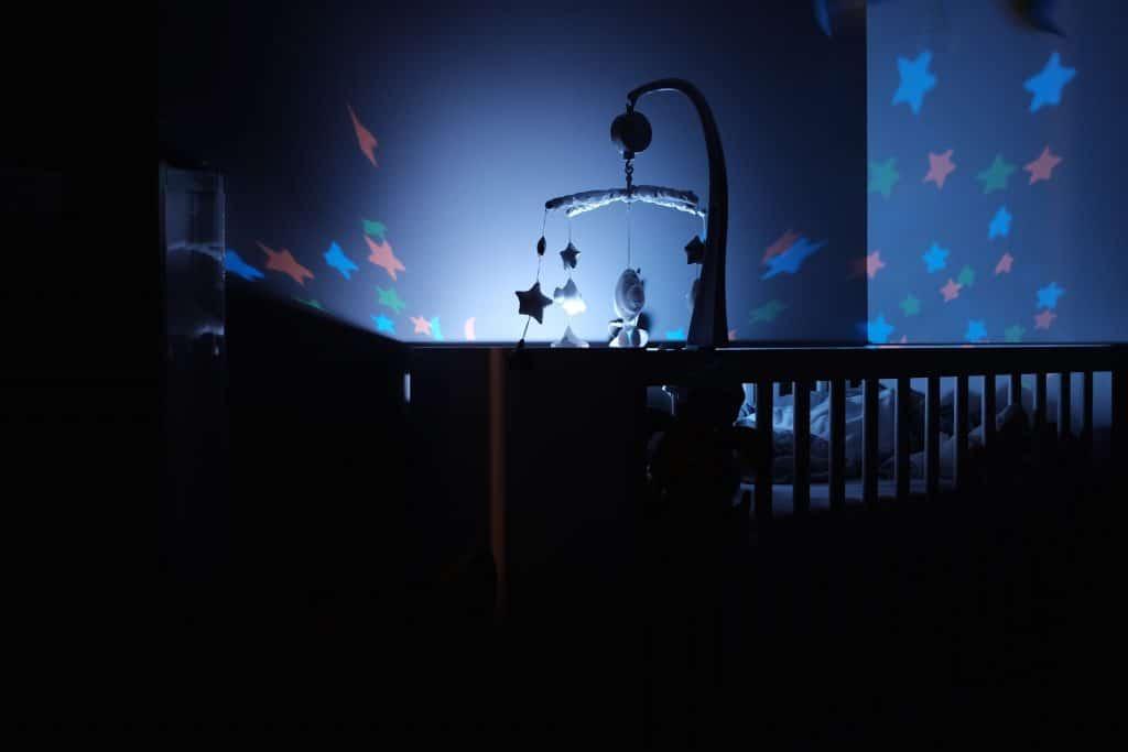 Mobile avec veilleuse suspendus au-dessus d'un lit de bébé